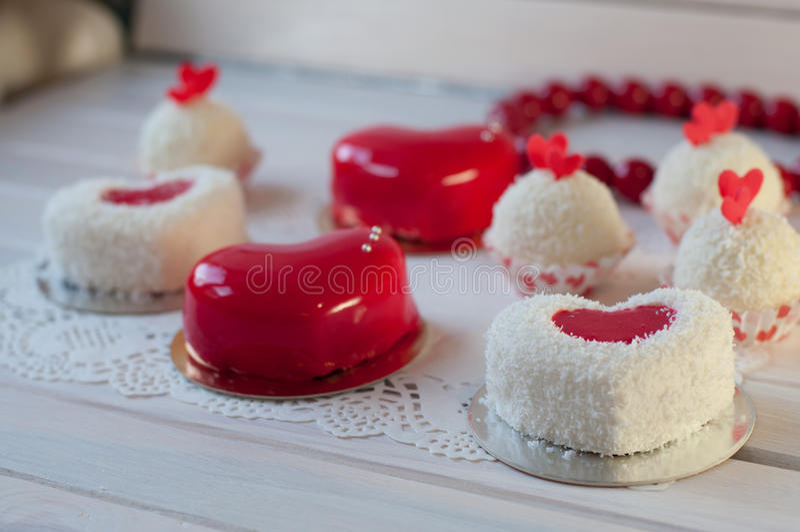 Κέικ διακοπών Οι κόκκινες, άσπρες καρδιές και οι σφαίρες βάζουν στις άσπρες ξύλινες επιτραπέζιες πλησίον χάντρες στοκ εικόνα