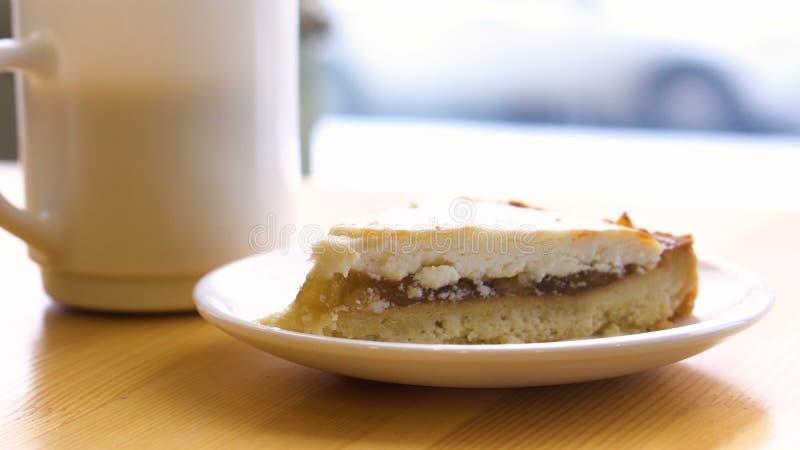 Κέικ και τσάι στον πίνακα από το παράθυρο στη καφετερία Εκλεκτική εστίαση Scone καφέ και σμέουρων στον ξύλινο πίνακα στοκ εικόνες με δικαίωμα ελεύθερης χρήσης