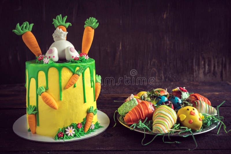 Κέικ και φράουλες Πάσχας που εξυπηρετούνται στο ξύλινο υπόβαθρο στοκ εικόνα με δικαίωμα ελεύθερης χρήσης