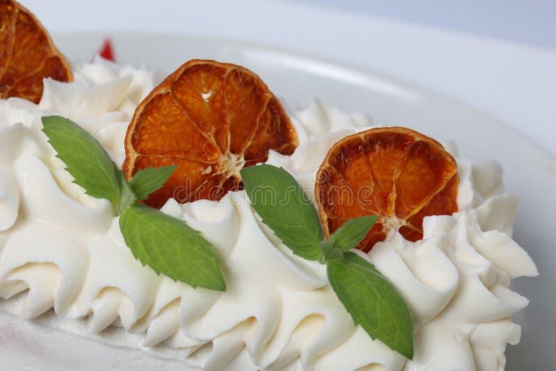 Κέικ κρέμας σφουγγαριών που ντύνεται με την κρέμα και που διακοσμείται με τις ξηρές πορτοκαλιές φέτες και τα φρέσκα φύλλα μεντών στοκ φωτογραφία