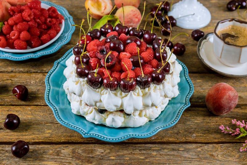 Κέικ μαρέγκας με τα μούρα και ένα φλιτζάνι του καφέ στοκ εικόνα