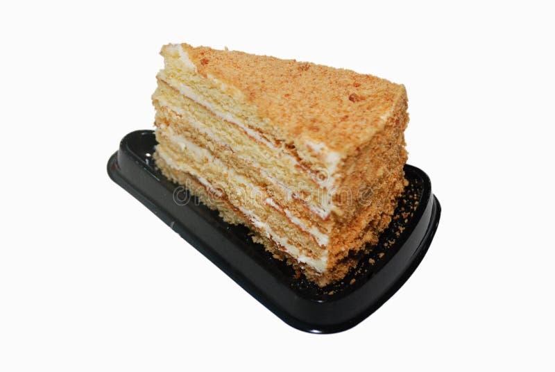 Κέικ μελιού με την κρέμα στη μαύρη πλαστική στάση διάθεσης στοκ φωτογραφία με δικαίωμα ελεύθερης χρήσης