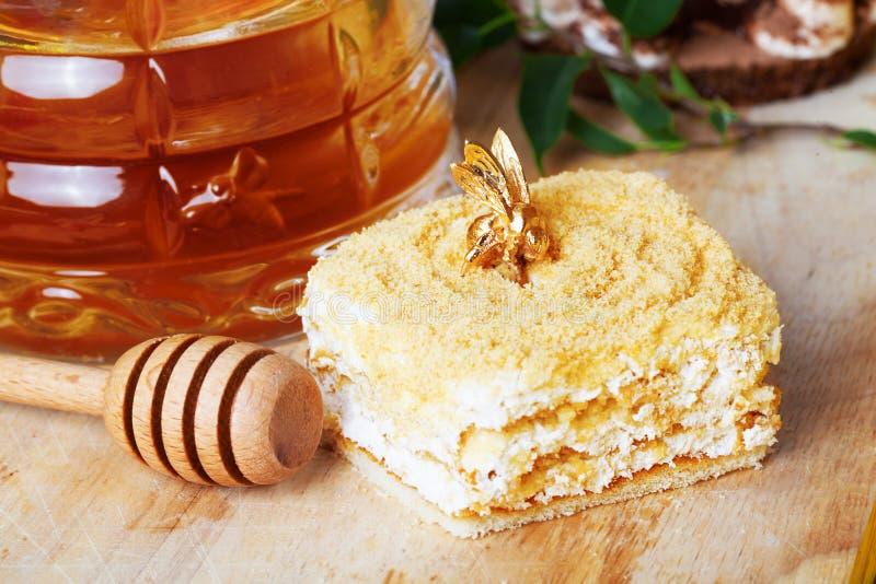 Κέικ μελιού, μέλισσα, ακόμα ζωή, κουτάλι, ραβδί, φωτεινός, σπιτικό, τρόφιμα στοκ εικόνες