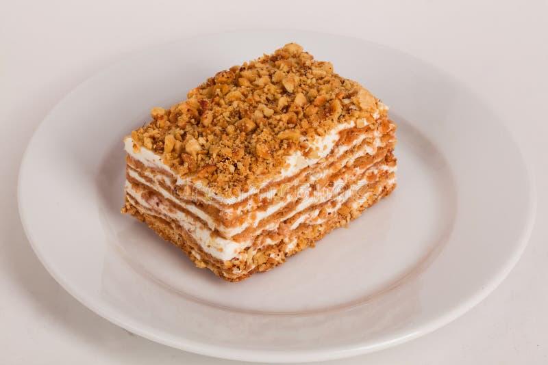 Κέικ μελιού σε ένα άσπρο υπόβαθρο πιάτων για τον καφέ στοκ εικόνες