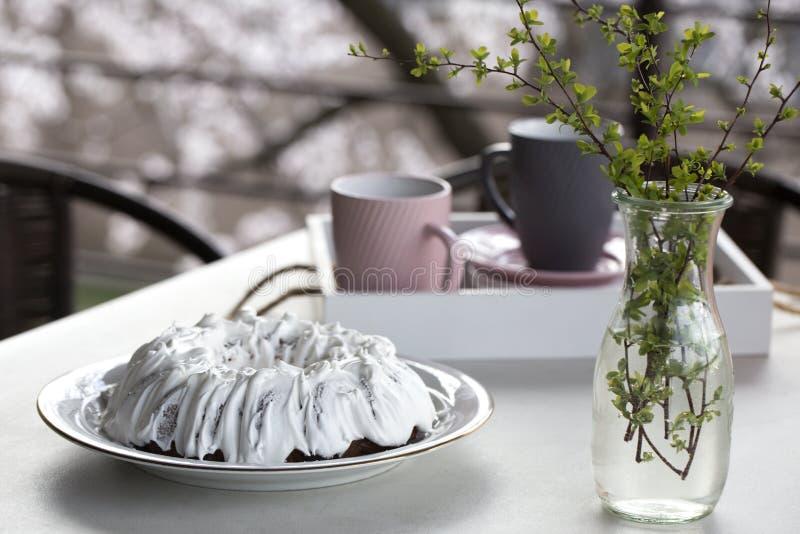 Σπιτικό κέικ με το τσάι Κέικ με την τήξη ζάχαρης Σπιτικό κέικ υπό μορφή δαχτυλιδιού με τα φλυτζάνια του τσαγιού ή του καφέ στον ά στοκ εικόνα με δικαίωμα ελεύθερης χρήσης