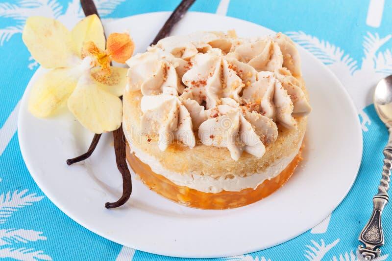 Κέικ με τη βανίλια, επιδόρπιο, ραβδιά, λουλούδι, ορχιδέα, σε μια κινηματογράφηση σε πρώτο πλάνο πιάτων, στρώματα κρέμας στοκ εικόνες