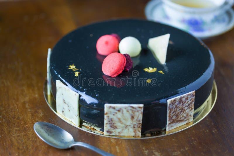 Κέικ με τη μαύρη τήξη και macaron στοκ φωτογραφία