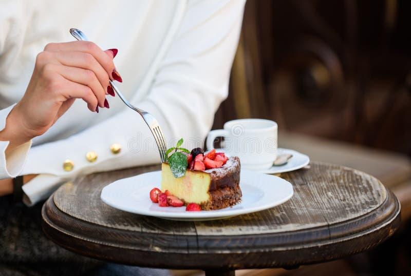 Κέικ με το εύγευστο επιδόρπιο κρέμας έννοια όρεξης Φλιτζάνι του καφέ κέικ επιδορπίων και θηλυκό χέρι με στενό επάνω δικράνων στοκ εικόνες