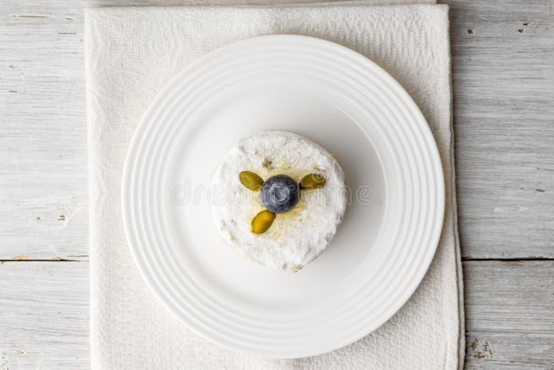 Κέικ με το φυστίκι και βακκίνιο στην άσπρη ξύλινη άποψη επιτραπέζιων κορυφών στοκ φωτογραφία