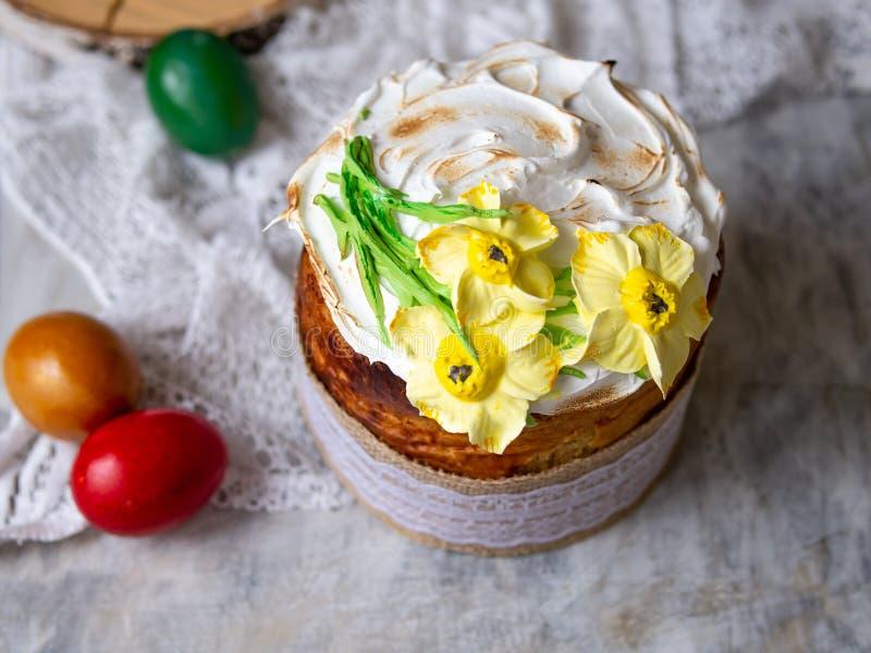 Κέικ Πάσχας kulich Το παραδοσιακό γλυκό ψωμί Πάσχας διακόσμησε τη μαρέγκα, κίτρινα daffodils στο ξύλινο γκρίζο υπόβαθρο με το ύφα στοκ φωτογραφίες με δικαίωμα ελεύθερης χρήσης
