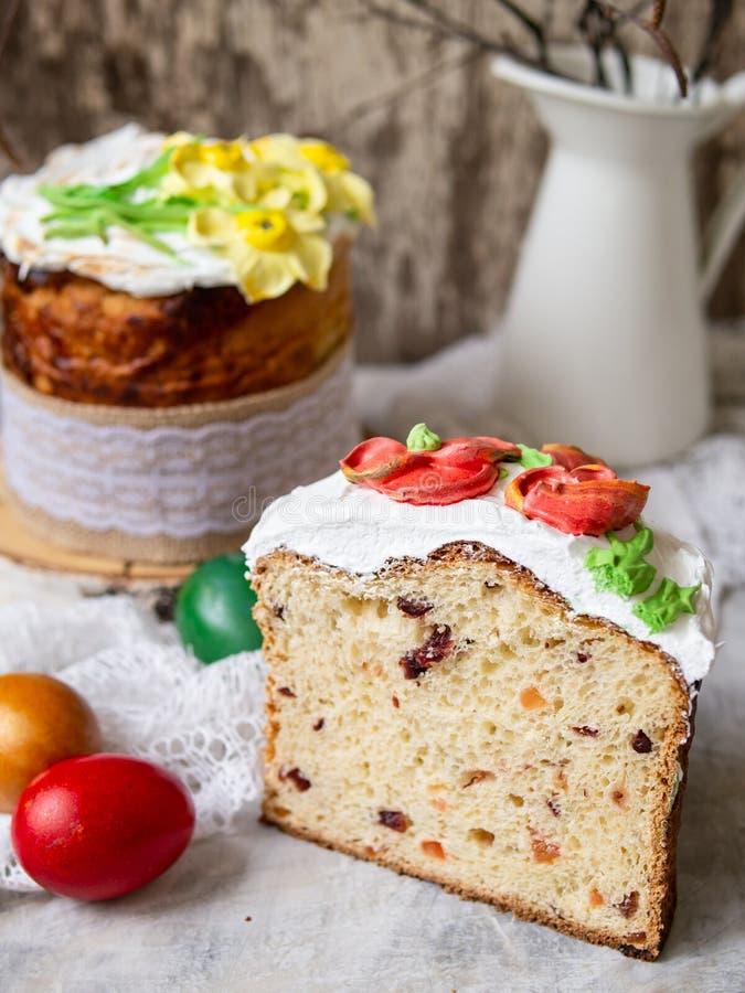 Κέικ Πάσχας kulich Το παραδοσιακό γλυκό ψωμί διακόσμησε τη μαρέγκα, κίτρινα daffodils στο γκρίζο υπόβαθρο με το ύφασμα δαντελλών  στοκ εικόνες