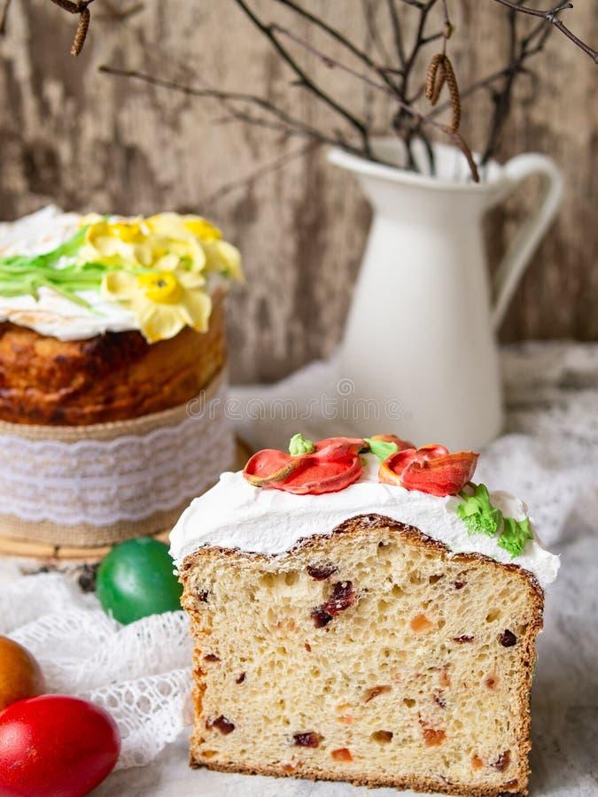 Κέικ Πάσχας kulich Το παραδοσιακό γλυκό ψωμί διακόσμησε τη μαρέγκα, κίτρινα daffodils στο γκρίζο υπόβαθρο με το ύφασμα δαντελλών  στοκ φωτογραφία με δικαίωμα ελεύθερης χρήσης