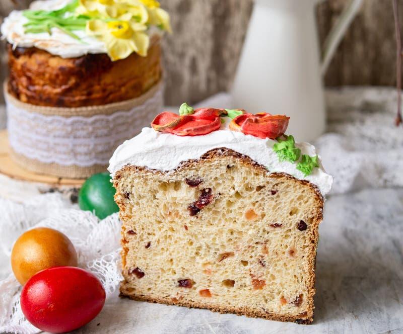 Κέικ Πάσχας kulich Το παραδοσιακό γλυκό ψωμί διακόσμησε τη μαρέγκα, κίτρινα daffodils στο γκρίζο υπόβαθρο με το ύφασμα δαντελλών  στοκ φωτογραφία