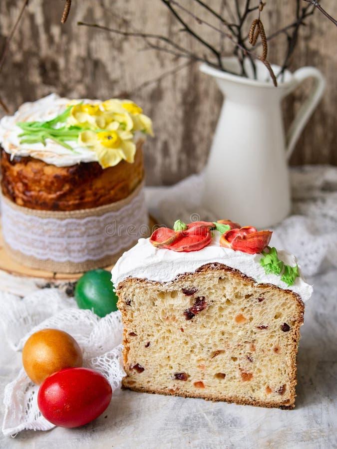 Κέικ Πάσχας kulich Το παραδοσιακό γλυκό ψωμί διακόσμησε τη μαρέγκα, κίτρινα daffodils στο γκρίζο υπόβαθρο με το ύφασμα δαντελλών  στοκ φωτογραφίες