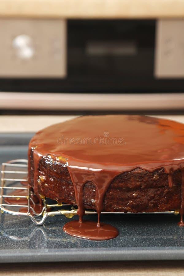 Κέικ που βάζει σε στρώσεις με την υγρή σοκολάτα στοκ φωτογραφία