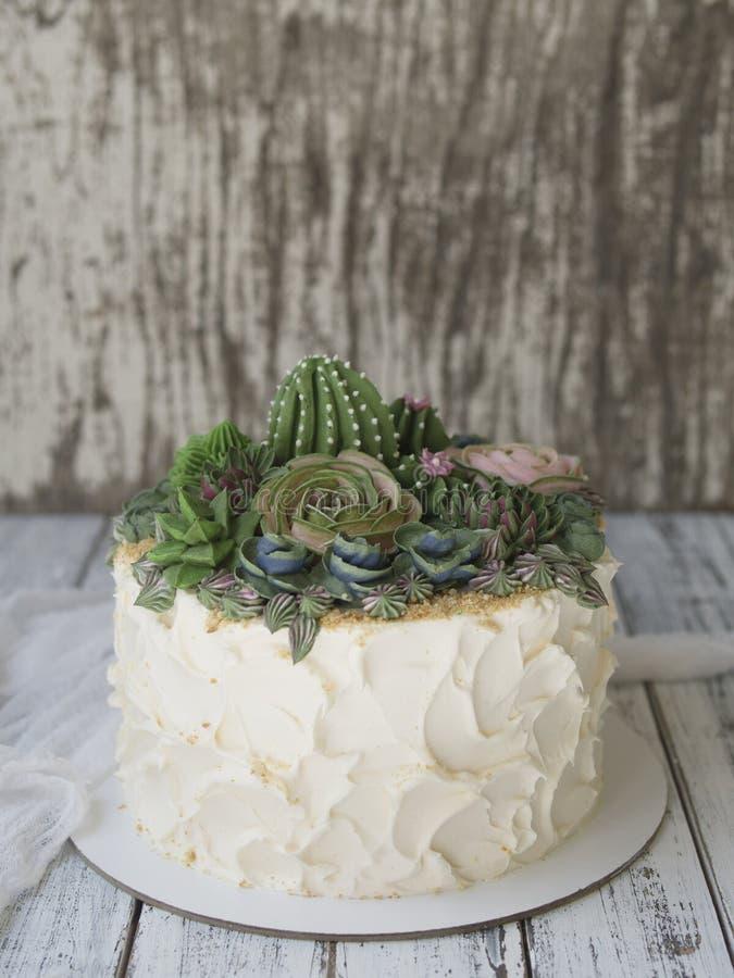 Κέικ που διακοσμείται με τα κρεμώδη succulents σε ένα ξύλινο υπόβαθρο με το άσπρο ύφασμα Το διάστημα αντιγράφων, κλείνει επάνω, τ στοκ εικόνα με δικαίωμα ελεύθερης χρήσης