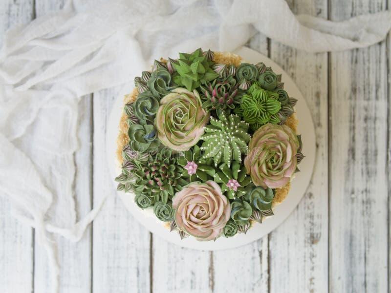 Κέικ που διακοσμείται με τα κρεμώδη succulents σε ένα ξύλινο υπόβαθρο με το άσπρο ύφασμα Το διάστημα αντιγράφων, κλείνει επάνω, τ στοκ εικόνα