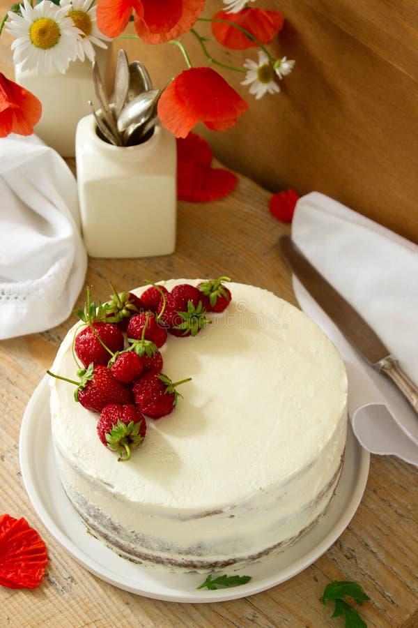 Κέικ που διακοσμείται με τις φράουλες σε ένα υπόβαθρο ενός βάζου με τα λουλούδια κάθετος στοκ φωτογραφία με δικαίωμα ελεύθερης χρήσης