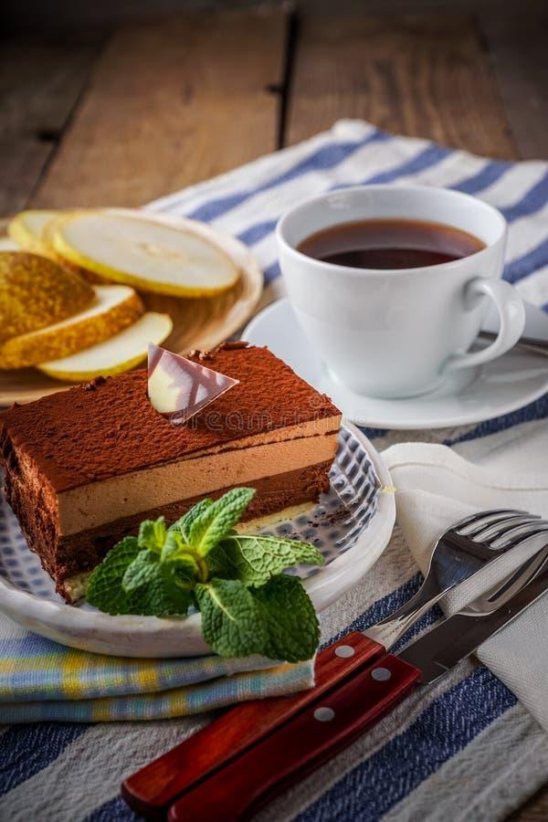 Κέικ σοκολάτας και ένα φλυτζάνι του τσαγιού με το λεμόνι, και φέτες του αχλαδιού, στοκ φωτογραφίες με δικαίωμα ελεύθερης χρήσης
