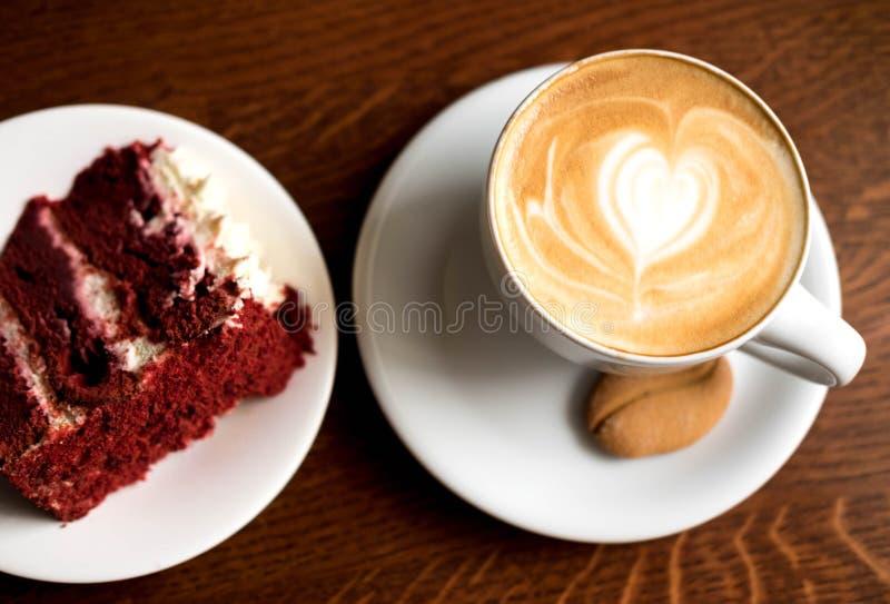 Κέικ σοκολάτας με ένα φλιτζάνι του καφέ στον πίνακα σε μια καφετερία Γλυκό πρόχειρο φαγητό στο μεσημεριανό γεύμα Γλυκά στοκ εικόνα με δικαίωμα ελεύθερης χρήσης
