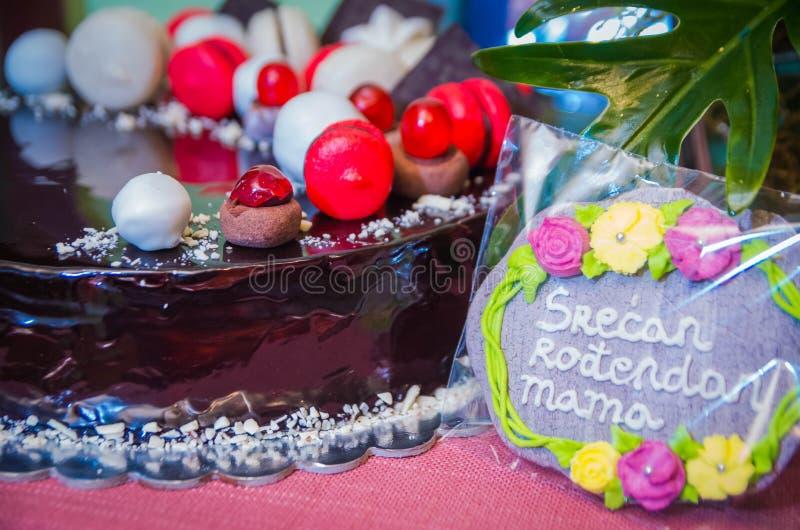 Κέικ σοκολάτας με τα κόκκινα και άσπρα γλυκά αμυγδάλων στην κορυφή στοκ εικόνα