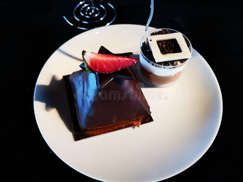 Κέικ σοκολάτας με τη φράουλα και κτυπημένη κρέμα με τον καφέ στοκ εικόνες