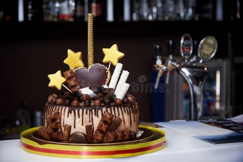 Κέικ σοκολάτας που διακοσμείται με τα γλυκά, τις καρδιές, τα αστέρια και ένα μπουκάλι στοκ εικόνες