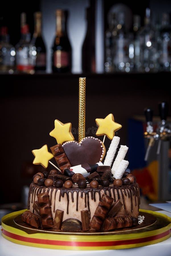 Κέικ σοκολάτας που διακοσμείται με τα γλυκά, τις καρδιές, τα αστέρια και ένα μπουκάλι στοκ φωτογραφία με δικαίωμα ελεύθερης χρήσης