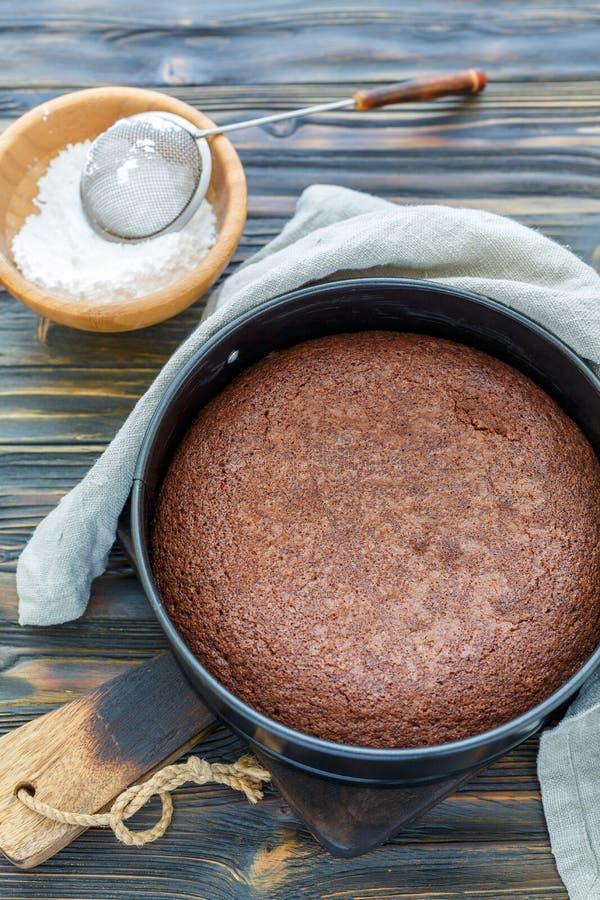 Κέικ σοκολάτας σε μια μορφή μετάλλων και κύπελλο με την κονιοποιημένη ζάχαρη στοκ εικόνες