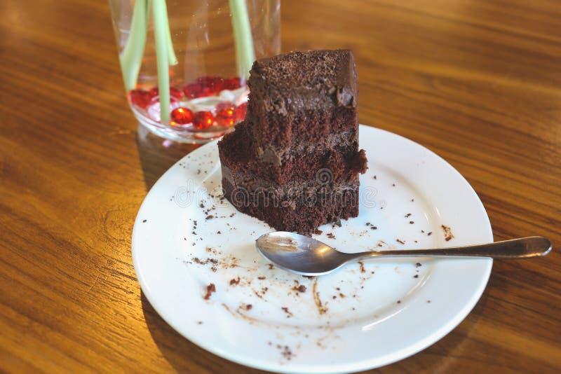 Κέικ σοκολάτας στο άσπρο πιάτο στον ξύλινο πίνακα στοκ εικόνα