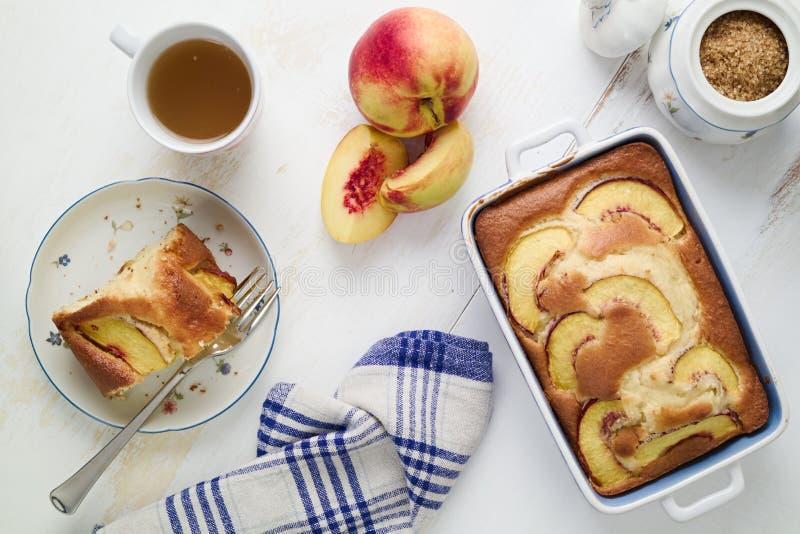 Κέικ σφουγγαριών γιαουρτιού διατροφής με τα ροδάκινα στον πίνακα Τρόφιμα Homebaked στοκ εικόνα με δικαίωμα ελεύθερης χρήσης