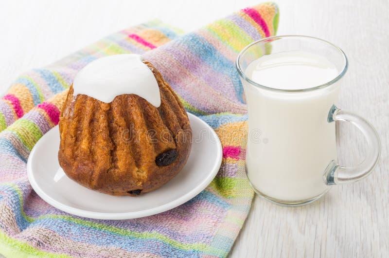 Κέικ σφουγγαριών με ρούμι-αρωματικός στο πιατάκι, φλυτζάνι του γάλακτος στοκ εικόνες
