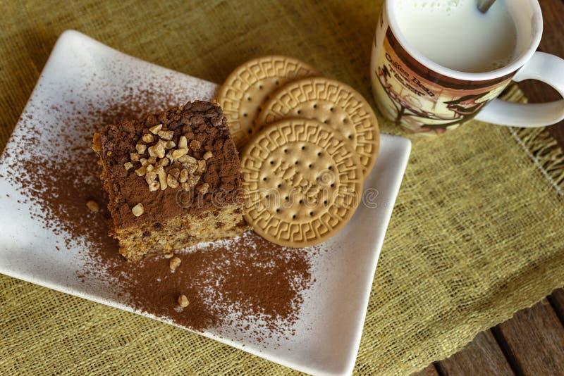 Κέικ σφουγγαριών μπισκότων και φλυτζάνι του γάλακτος στοκ φωτογραφία με δικαίωμα ελεύθερης χρήσης