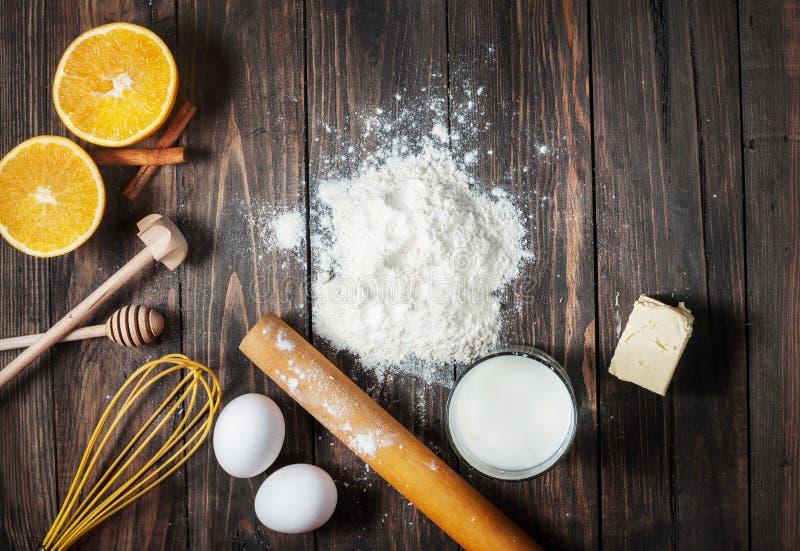 Κέικ ψησίματος στην αγροτική κουζίνα - συστατικά συνταγής ζύμης στον εκλεκτής ποιότητας ξύλινο πίνακα άνωθεν στοκ εικόνα