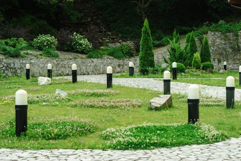 Κήπος με τη χλόη, τους θάμνους και τους λαμπτήρες στοκ εικόνες