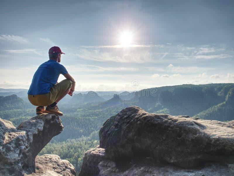 Κίνδυνος ατόμων στην άκρη Το άτομο στα αθλητικά ενδύματα κατάρτισης κάθεται στον απότομο βράχο στοκ φωτογραφίες με δικαίωμα ελεύθερης χρήσης