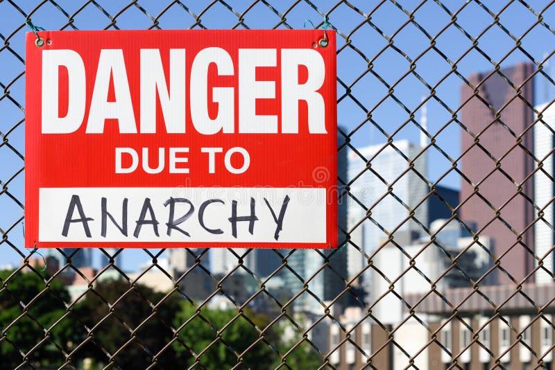 Κίνδυνος σημαδιών λόγω της ένωσης αναρχίας στο φράκτη στοκ φωτογραφίες
