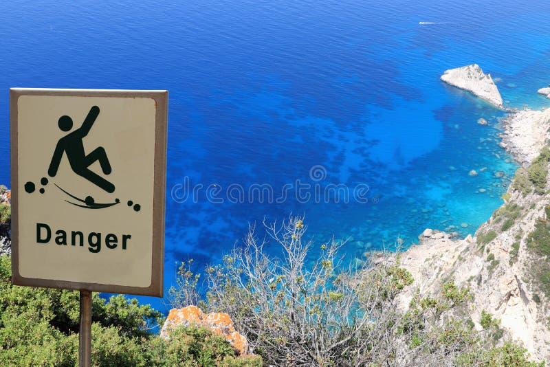 Κίνδυνος του μειωμένος σημαδιού κινδύνου κοντά σε έναν απότομο βράχο στοκ φωτογραφία με δικαίωμα ελεύθερης χρήσης