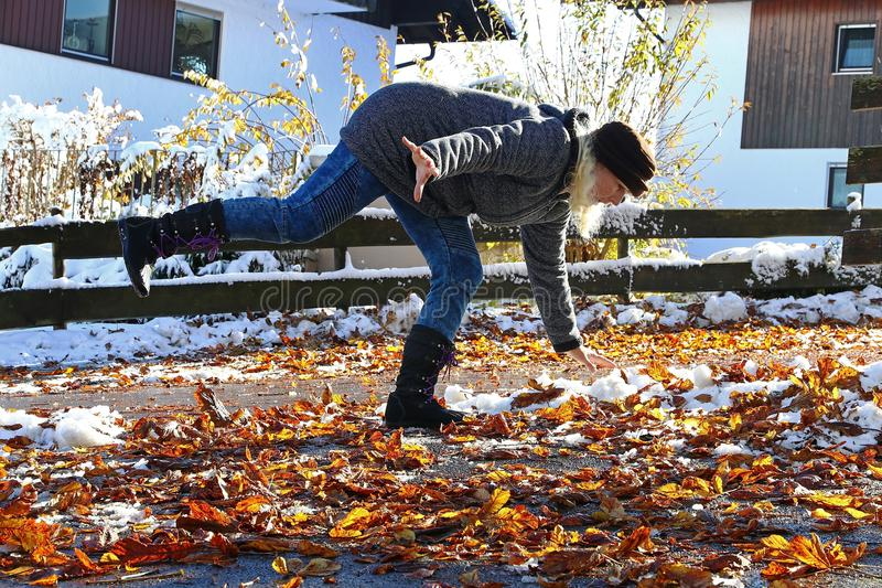 Κίνδυνος το φθινόπωρο και το χειμώνα Μια γυναίκα γλίστρησε στα υγρά, ομαλά φύλλα στοκ εικόνα