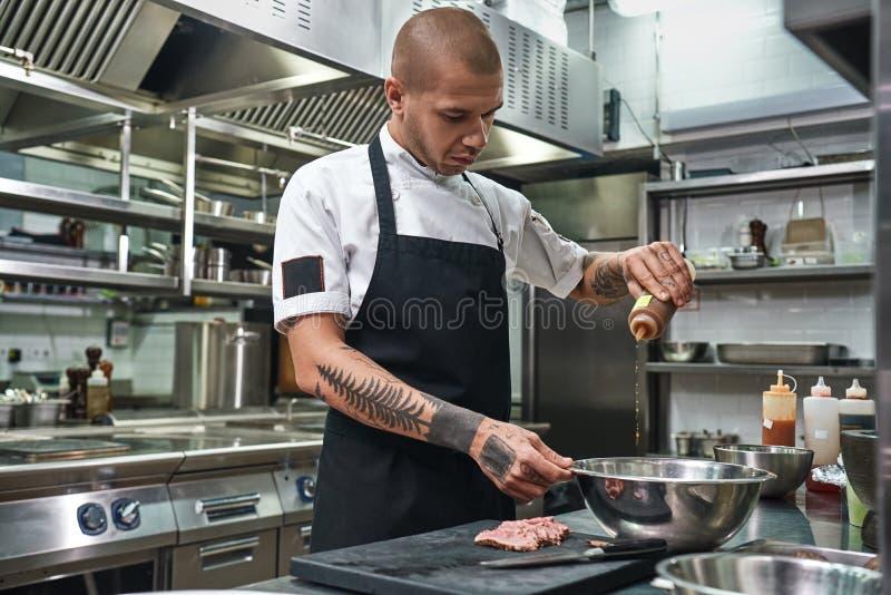 κίνηση αργή Όμορφος αρχιμάγειρας εστιατορίων στην ποδιά και με τις δερματοστιξίες στα όπλα του που προσθέτουν τη διάσημη σάλτσα τ στοκ εικόνα με δικαίωμα ελεύθερης χρήσης