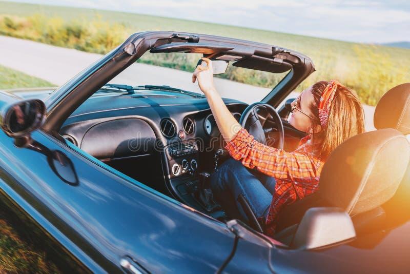 Κίνηση γυναικών ένα αυτοκίνητο καμπριολέ στοκ εικόνα
