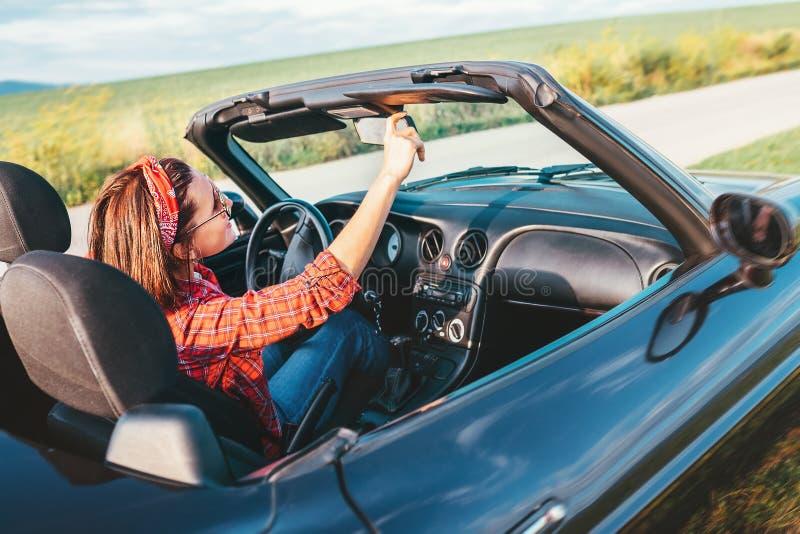 Κίνηση γυναικών ένα αυτοκίνητο καμπριολέ στοκ εικόνες