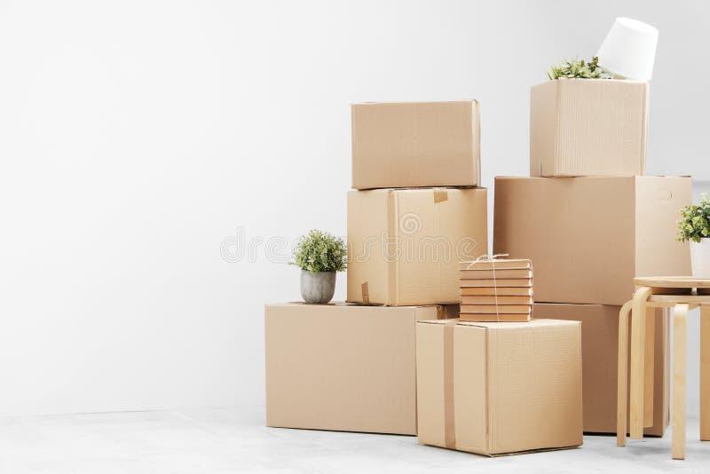 Κίνηση προς ένα νέο σπίτι Οι περιουσίες στα κουτιά από χαρτόνι, τις βίβλους και τις πράσινες εγκαταστάσεις στα δοχεία στέκονται σ στοκ εικόνες