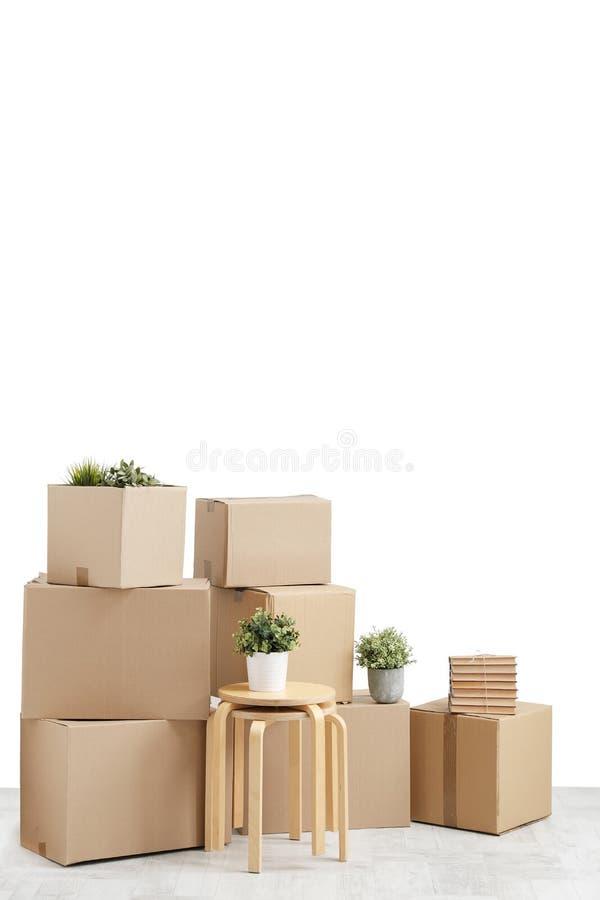 Κίνηση προς ένα νέο σπίτι Οι περιουσίες στα κουτιά από χαρτόνι, τις βίβλους και τις πράσινες εγκαταστάσεις στα δοχεία στέκονται σ στοκ εικόνες με δικαίωμα ελεύθερης χρήσης