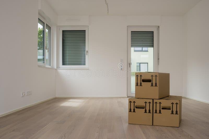 Κίνηση του συσκευάζοντας κιβωτίου στο κενές άσπρες δωμάτιο, τα παράθυρα και την πόρτα στο υπόβαθρο στοκ φωτογραφίες με δικαίωμα ελεύθερης χρήσης