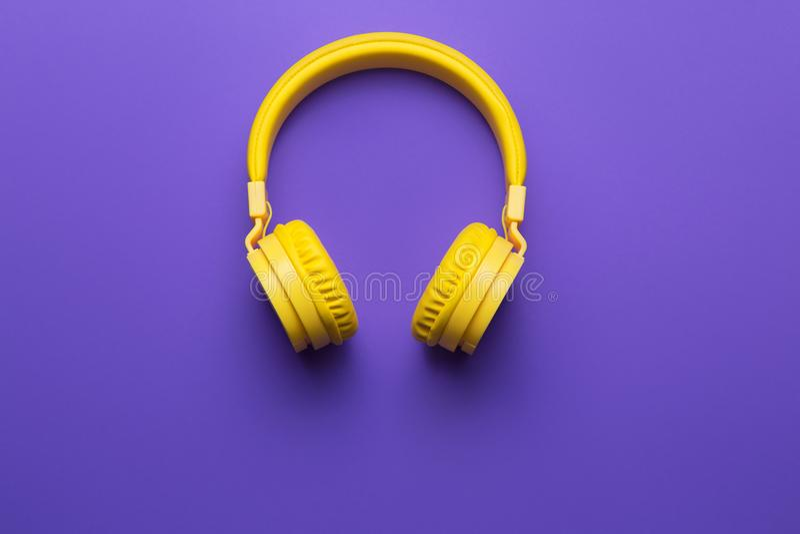 Κίτρινα ακουστικά στο πορφυρό υπόβαθρο ηλεκτρική μουσική απεικόνισης κιθάρων έννοιας στοκ φωτογραφία με δικαίωμα ελεύθερης χρήσης