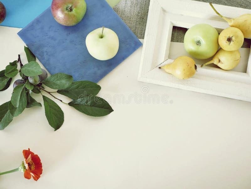 Κίτρινα αχλάδια και μήλα σε ένα άσπρο ξύλινο πλαίσιο, φύλλα, εποχιακή θερινή σύνθεση σε ένα ελαφρύ υπόβαθρο στοκ εικόνες