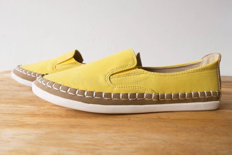 Κίτρινα παπούτσια μοκασινιών στον ξύλινο πίνακα στοκ φωτογραφίες