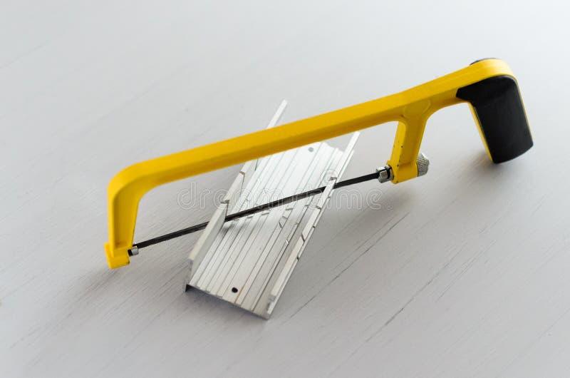 Κίτρινα πριόνι χεριών και miter αλουμινίου κιβώτιο για το χόμπι στο εγχώριο εργαστήριο στοκ φωτογραφίες