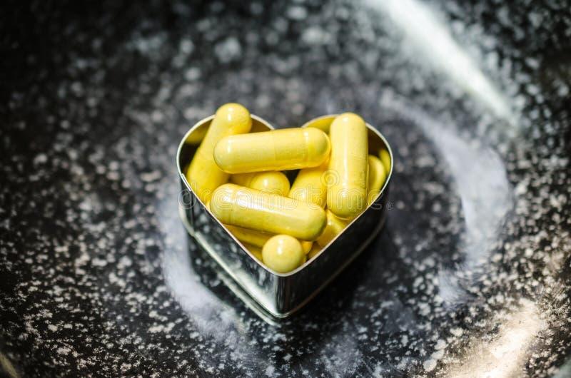 Κίτρινα τρόφιμα supplemnet CoQ10 στο μαύρο πιάτο στοκ φωτογραφίες